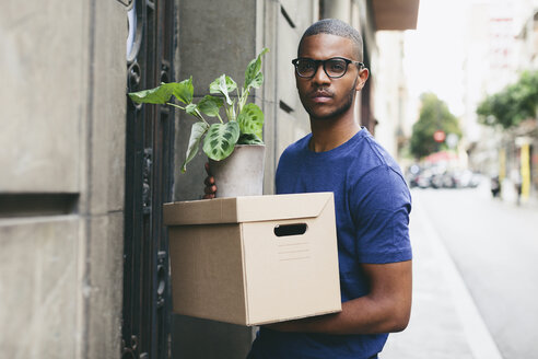 Spain, Barcelona, portrait of young man with cardboard box and foliage plant in front of a house - EBSF000815