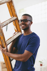 Portrait of smiling young man with ladder in his new flat - EBSF000820