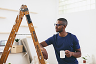 Young man leaning on step ladder having a coffee break - EBSF000822