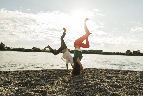 Playful young couple doing handstands by the riverside - UUF004997