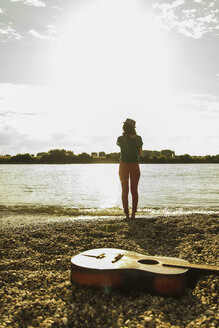 Young woman standing by the riverside with guitar in foreground - UUF005004
