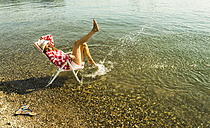 Young woman sitting on deckchair in river splashing with water - UUF005024