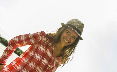 Portrait of happy young woman wearing hat outdoors - UUF005027