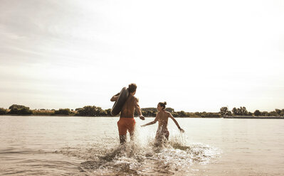 Young couple running with inner tube in river - UUF005045