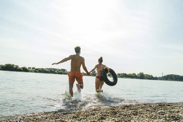 Young couple running with inner tube in river - UUF005046