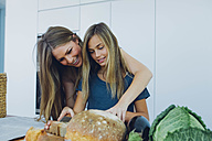Mother and daughter in kitchen preparing food - CHAF000839