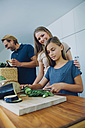 Mother and daughter in kitchen slicing cucumber with father in background - CHAF000843