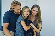 Portrait of smiling father, mother and daughter with puppy - CHAF000967