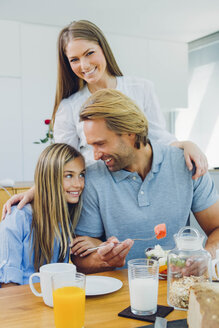 Happy mother, father and daughter at kitchen table - CHAF000865