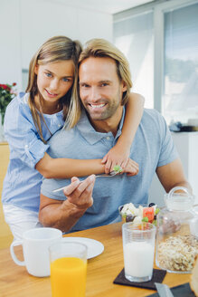Portrait of happy father and daughter at kitchen table - CHAF000866