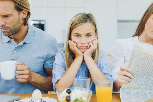 Frustrated girl with distracted parents at breakfast table - CHAF000874
