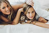 Happy mother and daughter under blanket - CHAF000875