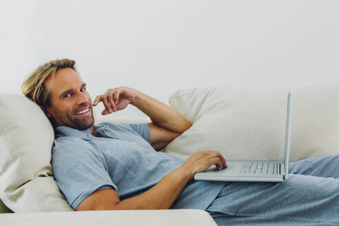 Smiling man lying on couch using laptop - CHAF000975