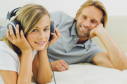 Girl lying on couch with father listening to music - CHAF000885