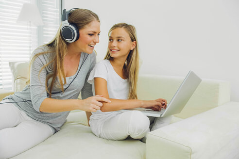 Mother and daughter on couch with laptop and headphones - CHAF000979