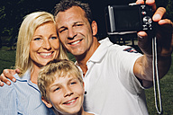 Happy family taking picture of themselves with a digital camera - CHAF000925