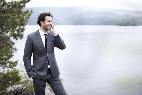 Germany, Rur Reservoir, smiling businessman at lakeshore on cell phone - MFRF000241