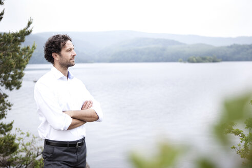 Germany, Rur Reservoir, relaxed businessman at lakeshore - MFRF000247