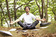 Germany, businessman in forest surrounded by papers practising yoga - MFRF000250