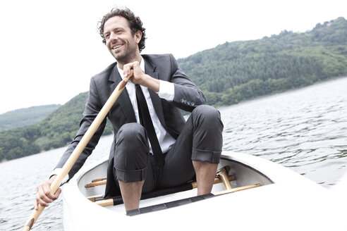 Germany, Rur Reservoir, smiling businessman in canoe - MFRF000258