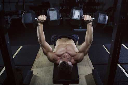 Physical athlete doing dumbbell bench presses - MADF000435