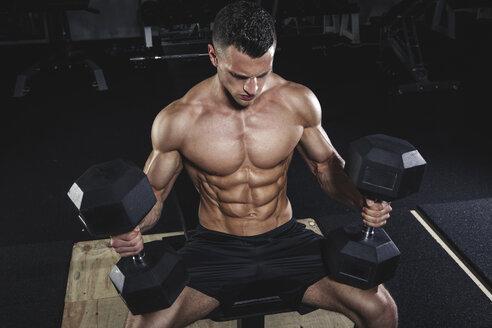 Physical athlete doing dumbbell bench presses - MADF000438