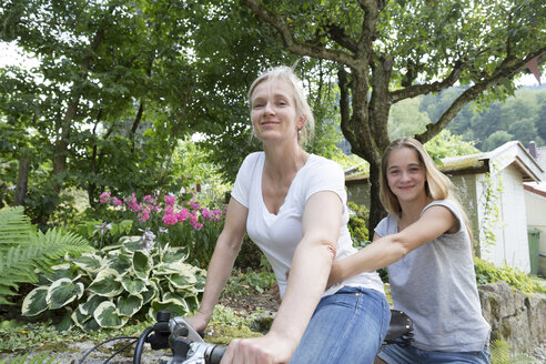 Mother and daughter riding on one bicycle - SGF001791