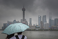 China, Shanghai, chinese couple with umbrella watching the skyline of pudong in rain - NK000328