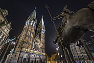 Germany, Bremen, Equestrian statue and Bremen Cathedral at night - NKF000334
