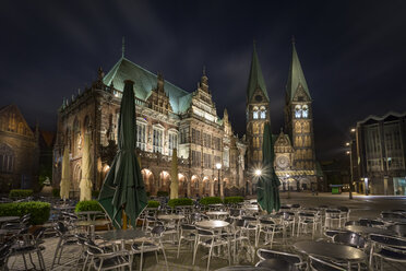 Germany, Bremen, view to townhall and Bremen Cathedral with sidewalk cafe in the foreground at night - NKF000336