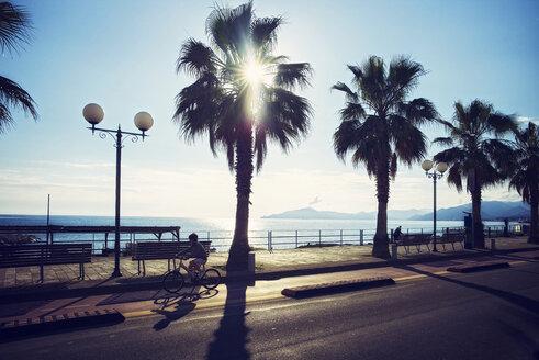 Italy, Liguria, Sestri Levante, boy on bicycle at waterfront promenade - DIK000166