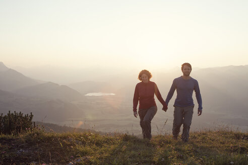 Austria, Tyrol, couple walking hand in hand at Unterberghorn at sunset - RBF002983