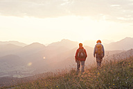 Austria, Tyrol, couple hiking at Unterberghorn at sunrise - RBF002956