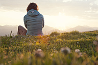 Austria, Tyrol, Unterberghorn, hiker resting in alpine landscape at sunrise - RBF002959