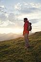 Austria, Tyrol, Unterberghorn, hiker standing in alpine landscape at sunrise - RBF002969