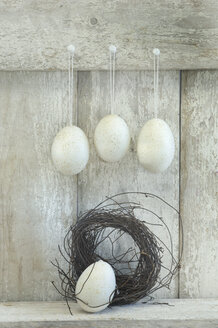 Easter eggs and nest in front of wooden shelf - ASF005640