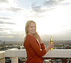 Germany, Berlin, portrait of smiling young woman with beverage - BFRF001403