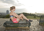 Germany, Munich, young woman after training sitting on a bench looking at view - FCF000707