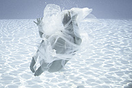 Young woman wrapped in cloth floating in water - FC000709