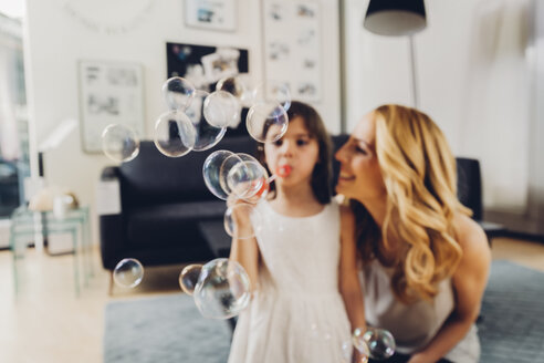 Happy mother with daughter at home blowing soap bubbles - CHAF000985