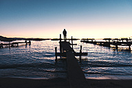 Bolivia, Man standing on wooden boardwalk looking the Titicaca Lake at sunset - GEMF000292