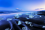 Iceland, view to glacial lake Jokulsarlon, glacier ice on beach at twilight - SMAF000356