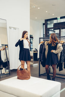 Two young women shopping in a boutique - CHAF001331