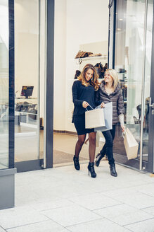 Two happy young women with shopping bags leaving a boutique - CHAF001351