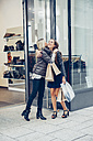 Two happy young women with shopping bags hugging outside a store - CHAF001363