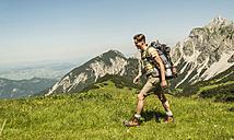 Austria, Tyrol, Tannheimer Tal, young man hiking on alpine meadow - UUF005053