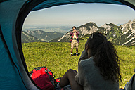Austria, Tyrol, Tannheimer Tal, young man taking picture of woman in tent - UUF005060