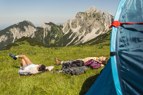 Austria, Tyrol, Tannheimer Tal, young couple resting next to tent on alpine meadow - UUF005064