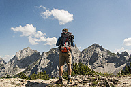 Austria, Tyrol, Tannheimer Tal, young man standing on mountain trail looking at view - UUF005066