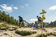 Austria, Tyrol, Tannheimer Tal, young couple hiking on mountain trail - UUF005069